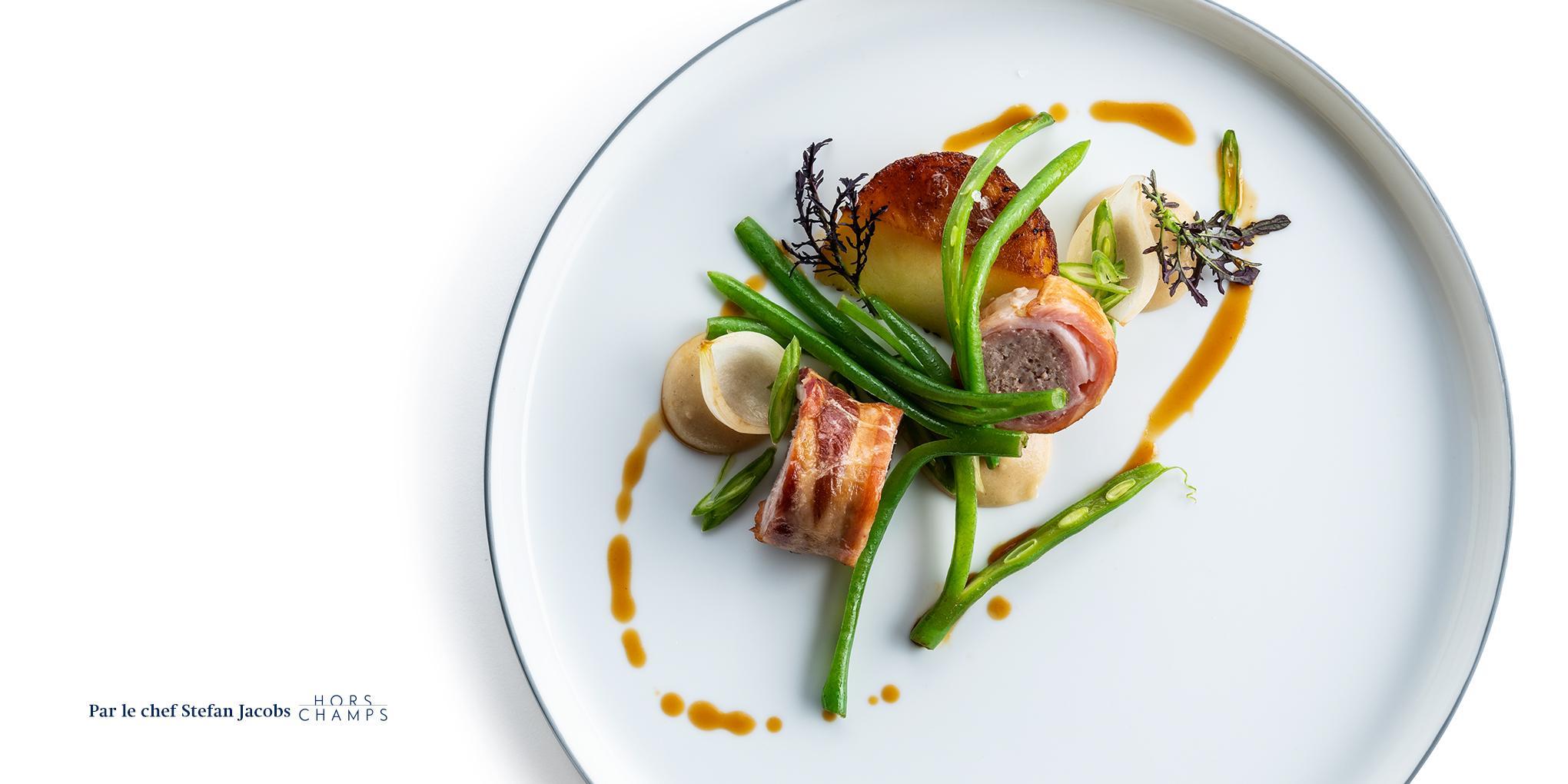 assiette blanche avec une cuisine gastronomique à la table d'un restaurant MICHELIN