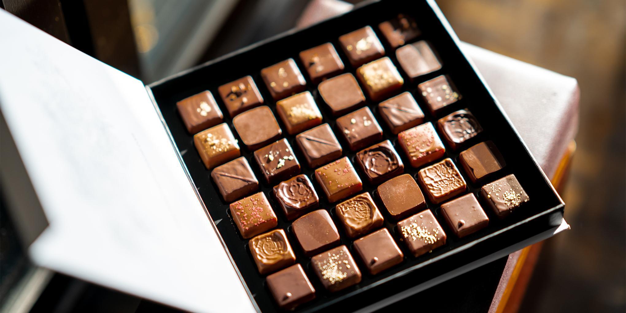 geopende doos van verschillende chocoladepralines op een donkere achtergrond