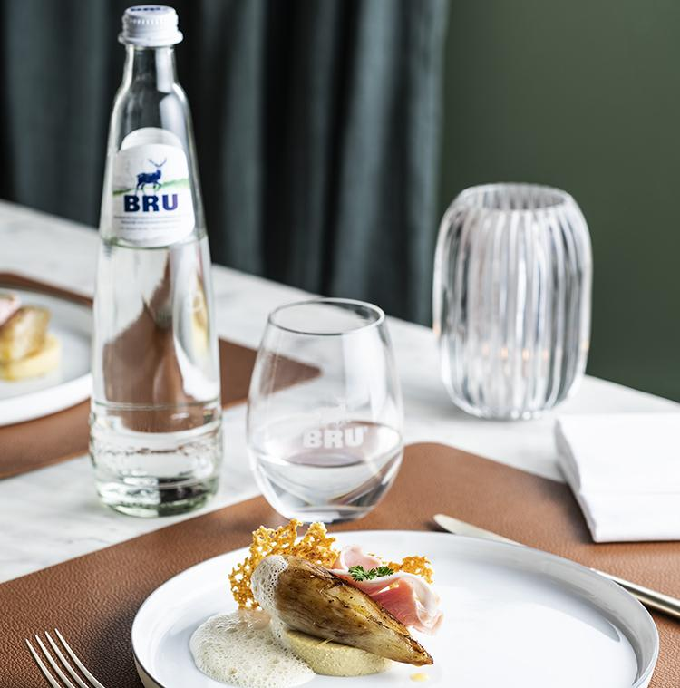 assiette avec de la cuisine locale et un verre d'eau BRU