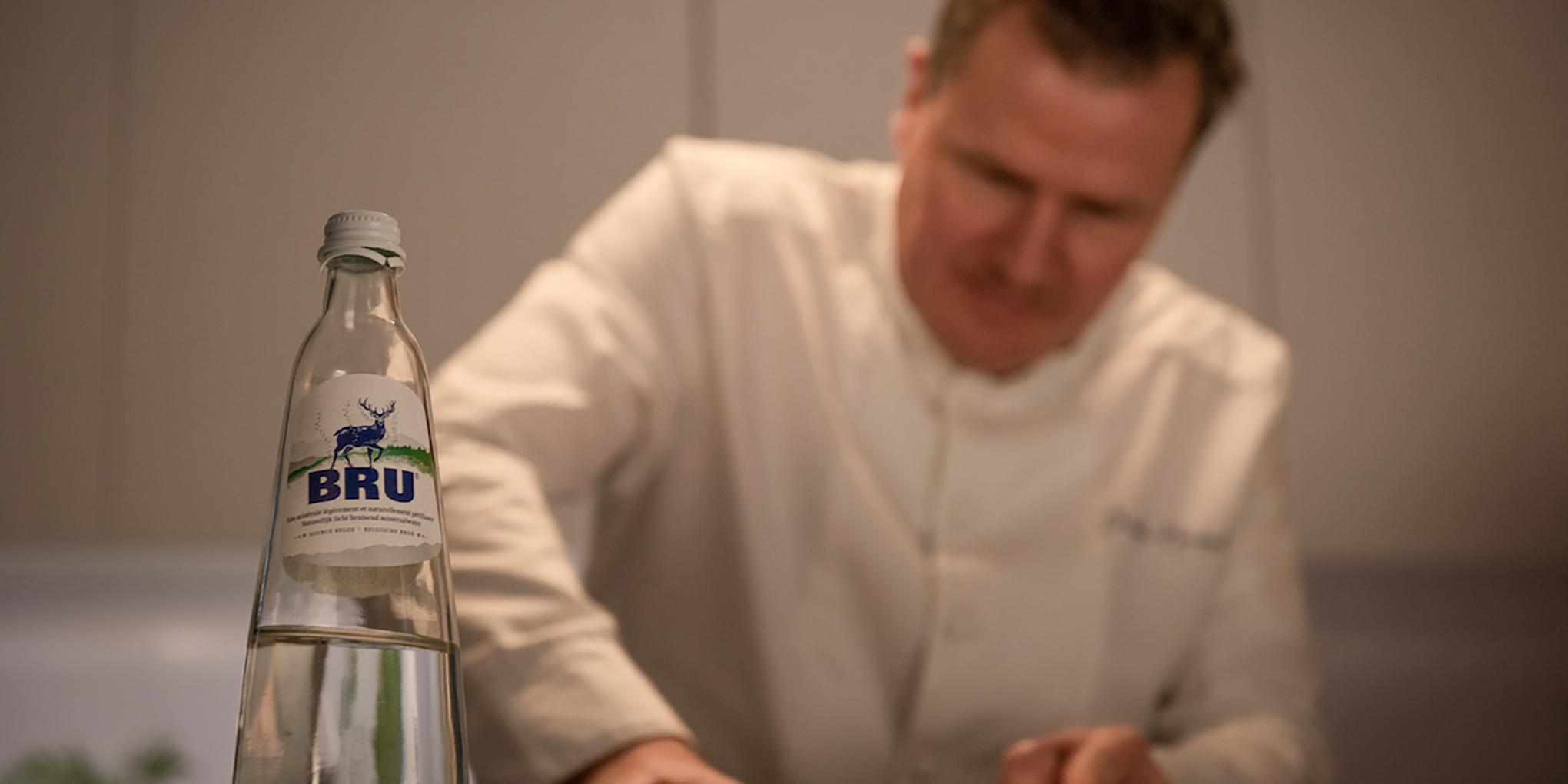 Christophe Hardiquest dans les cuisines de son restaurant Bon-bon avec une bouteille de BRU®