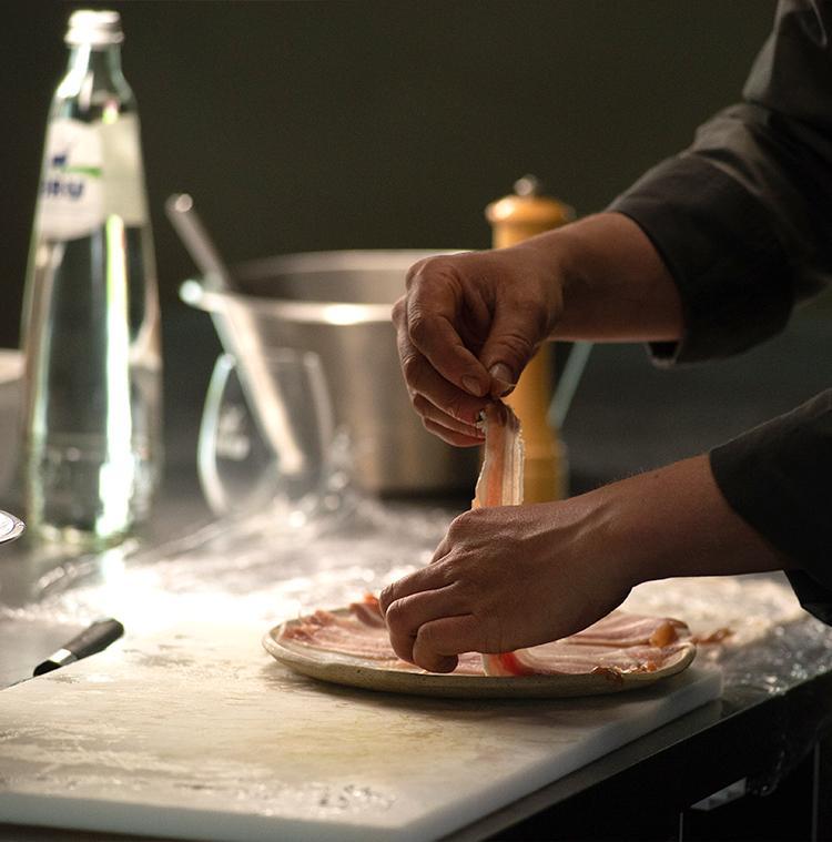 Le chef Stefan Jacobs dans sa cuisine, avec une bouteille de BRU®, prépare des paupiettes de porc pour sa version de la salade liégeoise.