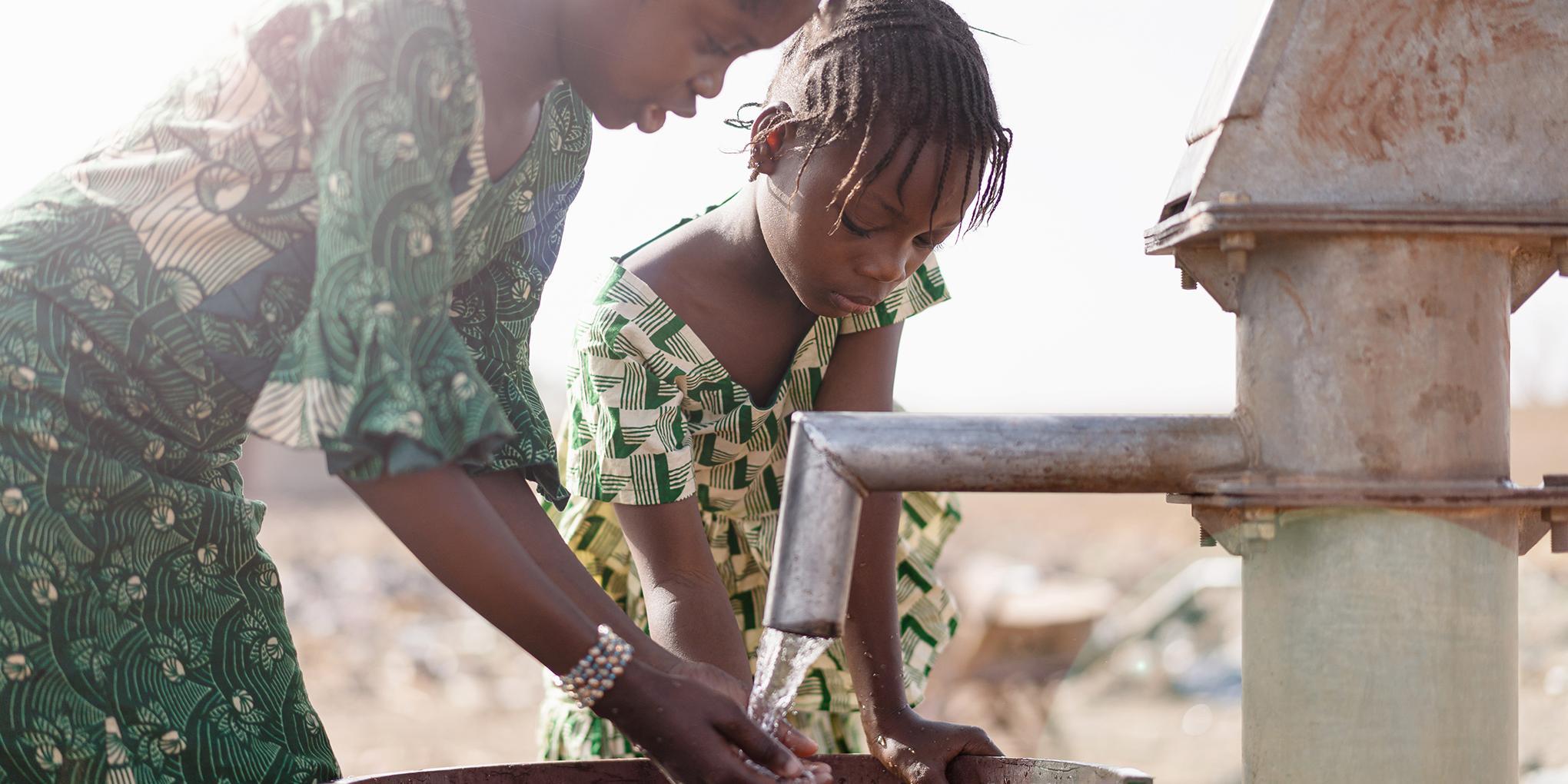 Kinderen pompen water uit een drinkwaterbron in Rwanda