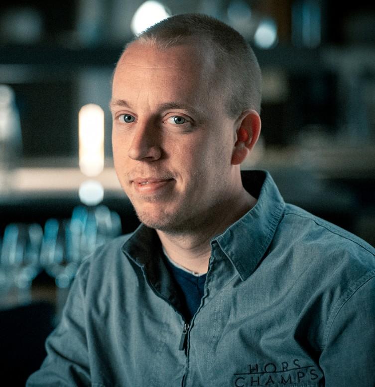Foto van de groene MICHELIN-sterrenchef Stefan Jacobs in de keuken van zijn restaurant Hors-Champs